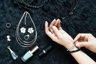 Bovenaanzicht van vrouwelijke handen met haar accessoires op zwarte wol