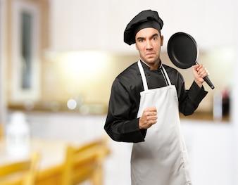 Boze jonge chef-kok met behulp van een kookgerei