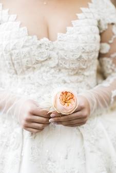 Bruid in rijke jurk houdt beige boutonniere