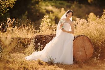 Bruid leunend op een grote houten stam