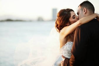 Bruidegom staat voor bruid terwijl ze haar sluier op de wind houdt
