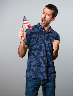 Brunette man die een Amerikaanse vlag op grijze achtergrond houdt