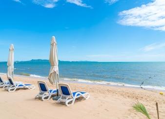 Buiten met paraplu en stoel op mooi tropisch strand en zee