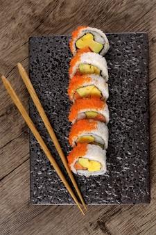 California roll sushi met stokjes op een zwarte plaat