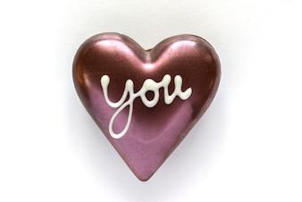 Chocolade hart gevormd met woord u op een witte achtergrond
