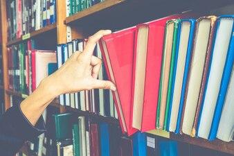 Close-up hand selecteren boek uit een boekenplank