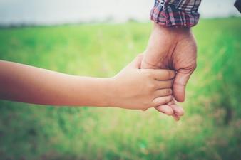 Close-up van de vader die zijn dochter de hand, zo lief, familie ti
