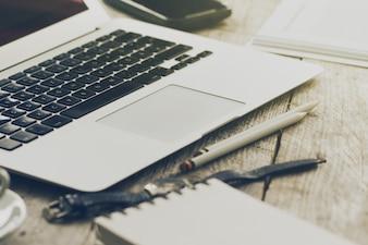 Close-up van werkruimte met moderne creatieve laptop, kopje koffie en potloden. Horizontaal met kopieerruimte.