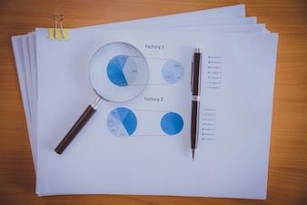 Controle van financiële verslagen. Grafieken en grafieken. Documenten en vergrootglas op grijze reflectie achtergrond.