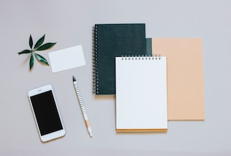 Creatieve platte lay-out van werkruimte bureau met smartphone, koffie en notitieboekje met kopie ruimte achtergrond, minimale stijl