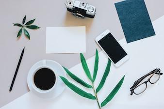 Creatieve platte lay-out van werkruimte bureau met smartphone, koffie, filmcamera, blanco papier en envelop met kopie ruimte achtergrond, minimale stijl