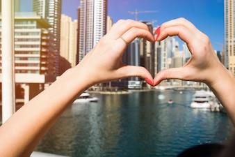 Dame met rode nagels toont hart met haar vingers voor wolkenkrabbers van Dubai