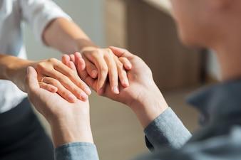 De jonge man met de handen van vriendin