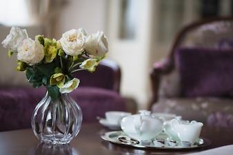 De kruik van het glas met bloemen en koffiekoppen