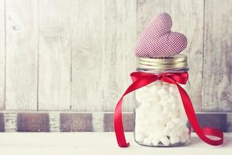 De kruik van het glas met marshmallows en een hart op de top