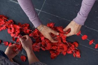 De mens zet rode rozenblaadjes op de draad