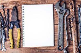 Diverse gereedschappen en het lege notitieboekje op een houten achtergrond