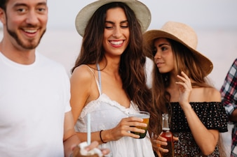 Drie vrienden met drankjes op een strandfeest