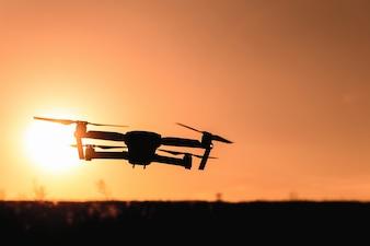 Drone silhouet met camera vliegen in het zonsondergang licht