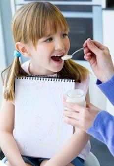 Een jonge vrouw en een meisje die yoghurt in de keuken eet
