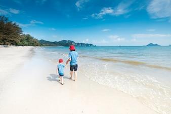 Een moeder en zoon op het strand buitenshuis Zee en Blauwe lucht
