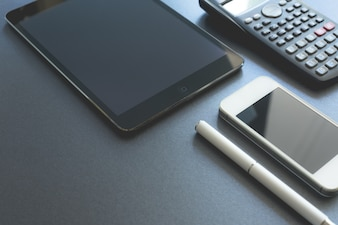 Enkele elektronische apparaten die op grijze achtergrond worden weergegeven. Slimme telefoon, pad en rekenmachine, alle digitale behalve een pen. Scène werkplek.