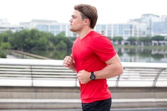 Ernstige Sportieve Jonge Man Running Outdoors