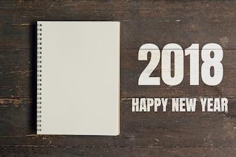 Gelukkig Nieuwjaar 2018 en Bruin notitieboekje open op houten tafel achtergrond met ruimte.