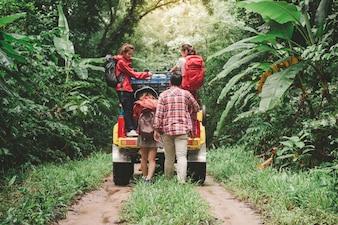 Gelukkige Aziatische jonge reizigers met 4WD rijden auto weg in het bos, jong koppel met rugzakken lopen en nog twee genieten van 4WD rijden auto. Jonge gemengd ras Aziatische vrouw en man.