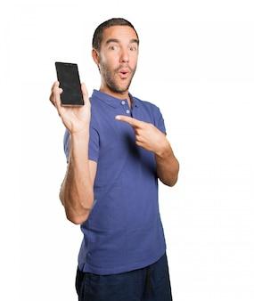 Gelukkige jonge man met behulp van een mobiele telefoon op een witte achtergrond