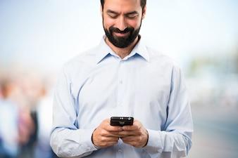 Gelukkige knappe man met baard praten met mobiel op ongerichte achtergrond