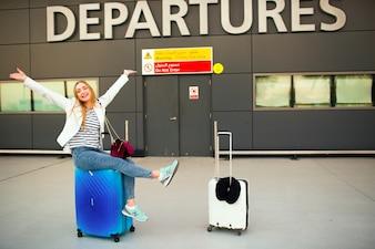 Gelukkige vrouw verhoogt haar handen omhoog op de blauwe koffer te zitten