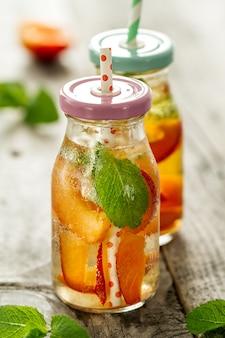 Gezond smakelijk vers verfrissend detoxwater in flessen of potten met abrikozen, munt en ijs op houten achtergrond. Detailopname. Gezond Leven Concept.