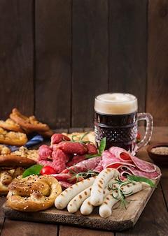 Glas bier, pretzels en diverse worstjes op houten achtergrond. Oktoberfest.