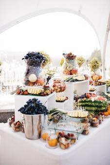 Glas vaas met druivenstok op tafel met fruit