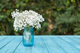 Glazen vaas met witte bloemen op blauwe houten tafel