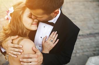 Glimlachende bruid die haar echtgenoot omhelst