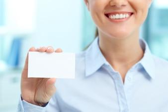 Glimlachende onderneemster met leeg adreskaartje