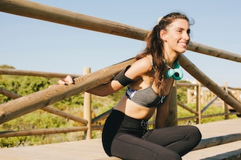Glimlachende vrouw die zich uitstrekt bij hek