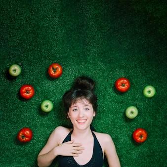 Glimlachende vrouw in de buurt van appels en tomaten