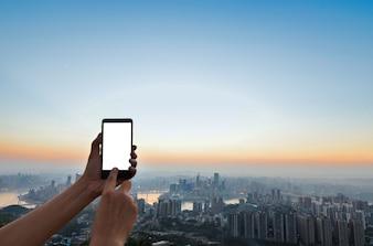 Hand aanraken van een mobiele scherm met de stad achtergrond