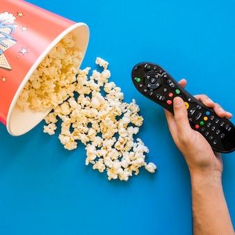 Hand met afstandsbediening en emmer popcorn