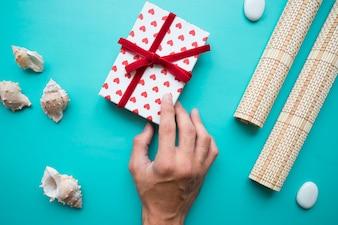 Hand met geschenkdoos en decoratieve elementen