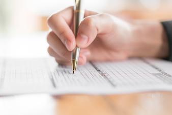 Hand met pen over het aanvraagformulier.