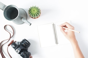 Hand van de vrouw die potlood op lege notitieblok met filmcamera, pot van cactus en vintage watering, geïsoleerd op witte achtergrond, bovenaanzicht, vlakke lay