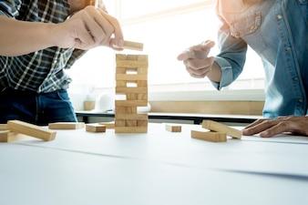 Hand van ingenieur die een blokken houten toren spel (jenga) speelt op blauwdruk of architectonisch project