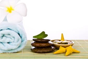 Handdoek met stenen op een tafel van riet