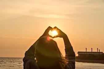 Handen die een hartvorm vormen met zonsondergangssilhouet