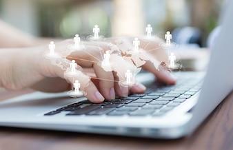 Handen met laptop en virtuele kaart van de wereld