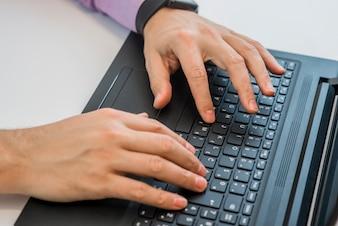 Handen typen in een laptop bovenaanzicht